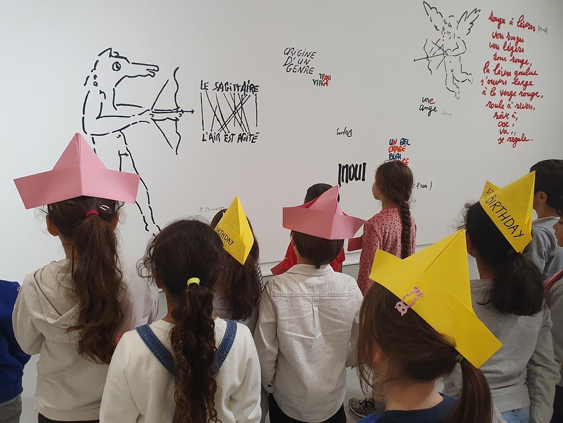 Enfants lors de la Chasse aux indices dans le cadre de l'Anniversaire de l'Art inspiré de Robert Filliou. Oeuvre de Jean Dupuy au second plan.